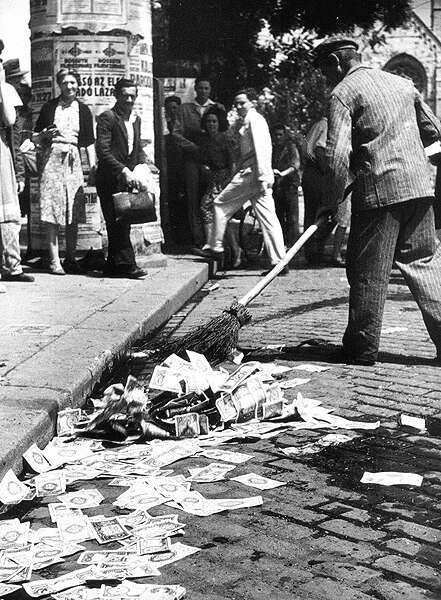 Sweeping up the banknotes from the street after the Hungarian pengő was replaced in 1946. / wiki commons