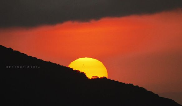 Solar spot visible as sun goes down behind Cerro Turrubares, Costa Rica, by  Bernal Saborio / Wikimedia *